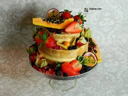 Semi Naked Wedding Cake With Tropical Fruit Berries And Pomegranate Jewels