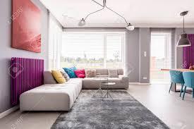 abstrakte malerei die über einem purpurroten heizkörper hängt und ein großes sofa mit vielen bunten kissen in einem stilvollen wohnzimmer