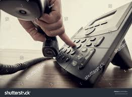 Closeup of male hand holding telephone receiver and dialing a phone number on a classical black