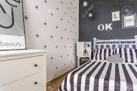 schlafzimmer neuer stil in schwarz und weiß mit weißen kommode tafel wand und muster bettwäsche