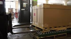 A Forklift In Warehouse Is Used To Place Box Onto Turntable Which Will