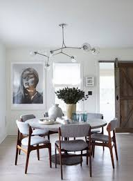 Modern Dining Room With Round Table Gray Upholstered Chairs And A Globe Light Fixture