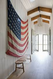 All White Wood Paneled Wall And Ceiling With Natural Floors A Rustic Bench Giant American Flag As Art I Love How Its Hung Only Two Nails