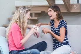 zwei schöne frauen die eine tasse kaffee und reden im wohnzimmer zu hause