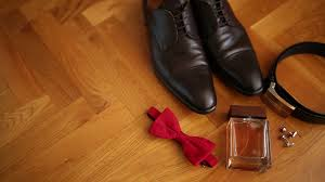 Brown Mans Shoes With Laces Black Leather Belt Krsany Bow Tie Cufflinks And Cologne Lie On The Wooden Floor Stock Video Footage