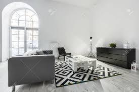 weißes wohnzimmer mit grauem sofa palettentisch und schwarzem schrank