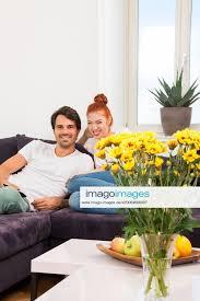 stockfoto junges liebespaar sitzt im wohnzimmer auf der