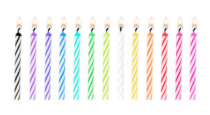 Set of rainbow color birthday or party candles were lit and isolated on white background with