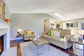 gemütliches wohnzimmer mit parkettboden kamin und beige sofa offenes wohnzimmer zur küche verbunden