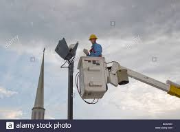 replacing parking lot light bulb from truck stock photo