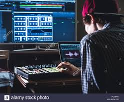 Young Male Sound Engineer Working In Professional Music Studio With Modern Equipment Recording New Track