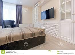 schlafzimmer in den hellen farben mit dunklem bett und