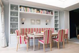 View In Gallery Banquette Seating For The Scandinavian Dining Space With Smart Shelves All Around And Colorful Chairs