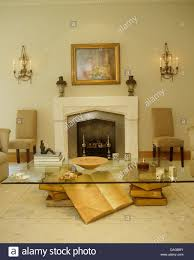 glass coffee table and book sculpture in modern living room with