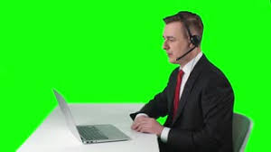 TV Reporter Sitting At Desk In Front Of Laptop Looking Screen And Talking