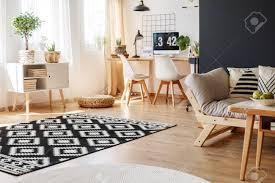 schwarz weißer teppich und beige sofa im multifunktionalen wohnzimmer mit gemütlichem arbeitsbereich