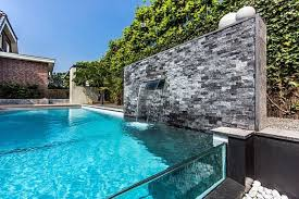 Modern Above Ground Swimming Pool With Glass Wall And Waterfall Ideas