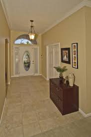 Interior High Ceiling Foyer Lighting With Two Framed Paintings Wooden Chest Drawer And Glass Door