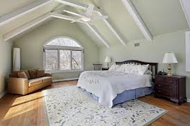 Vaulted Ceiling With Exposed Painted White Beams Stand Over Light Hardwood Floor And Floral Rug In