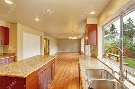 küche mit hellen holzschränke und granitplatten küche zimmer verfügt über küche insel leeres wohnzimmer