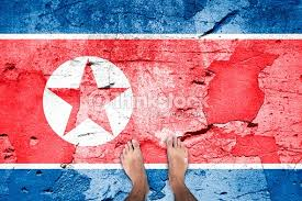 Top View Of A Barefoot Man Stands On Damaged Cracked Cement Floor Painted With North Korea