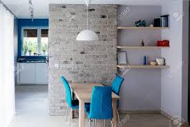 moderne esszimmer mit holztisch türkis lederstühle alte leere graue mauer und regale