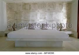 king size bett mit marmor plattform gegen fliesen wand in