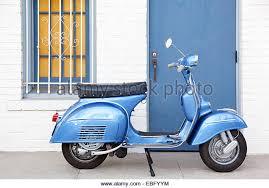 Profile Of Light Blue Vespa Scooter Infront Building