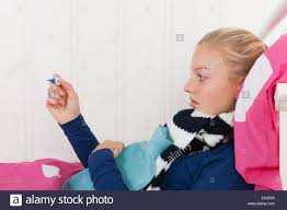 sick teen laying in bed with thermometer for the temperature