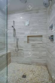 perfekt gestaltete nahtlose glasdusche mit grauen marmorwänden die eine nische einrahmen und eine moderne messingduschkabine über einem