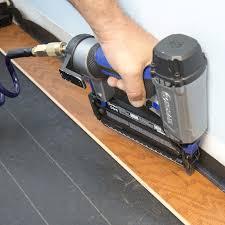 Staple Gun Securing First Row Of Engineered Wood Flooring