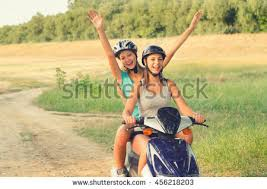 Two Smiling Happy Teenage Girls Riding Scooter Motorcycle On Sunny Summer Day