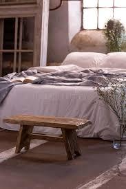 holzbank vor bett mit decke im natürlichen schlafzimmer