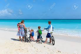 Happy Young Family With Kids Riding Bikes On Beach Stock Photo