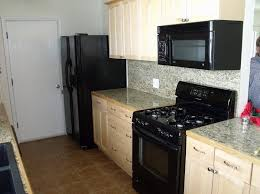Off White Kitchen Cabinets With Black Appliances Wall Mount Microwave Granite Countertops Also Stainless Steel Electric Range And Maple