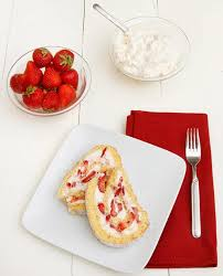 slices of a strawberry shortcake roll on a white plate with a red napkin and a