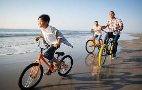 Family Bike Riding On Beach