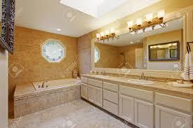 luxus badezimmer interieur mit fliesenverkleidung und großen waschbeckenunterschrank mit zwei waschbecken und großem spiegel