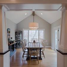 Dining Room With Large Farm Style Table Vaulted Ceilings And View Of Woods