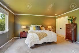 grauer schlafzimmerinnenraum mit kommode und frischen blumen großes bett mit weißer bettwäsche und gelben kissen nordwesten usa