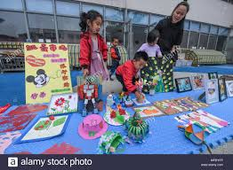 Children Arrange Paper Cuttings And Handicrafts In A Charity Bazaar During Campus Cutting Festival At Kindergarten Changxing County