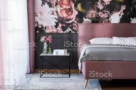 blumen am tisch neben rosa bett mit grauen blättern im schlafzimmer innenraum mit tapete echtes foto stockfoto und mehr bilder bett