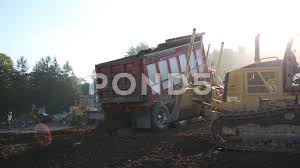 Dump Truck Empties Load And Mini Dozer Moves Load ~ Video #69247915