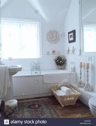 korb mit handtuch neben weiß verkleidete bad im weißen land