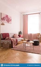 couchtische und alte schulpuff auf rosa pastellteppich im