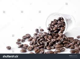 Spilled Coffee Beans From The Transparent Cup Isolated Over White Background