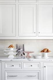 the backsplash in this kitchen is classic white subway tiles and