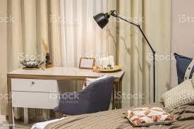 ein moderner raum für einen im skandinavischen stil ein bett einen schreibtisch einen sessel gardinen ein modernes schlafzimmer und