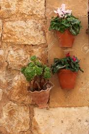 Hanging Plant Pots With Flowers Mounted On A Rustic Old Stone Wall Background Image Stock