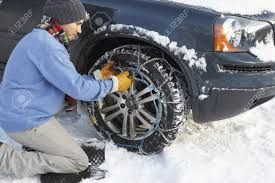 Man Putting Snow Chains Onto Tyre Of Car Stock Photo, Picture And ...